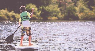 Kind auf einem Standup Paddleboard