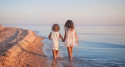 Zwei Kinder gehen am Strand entlang