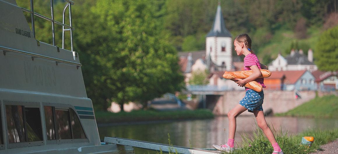 Das Mädchen bringt ein ofenfrisches Baguette an Bord