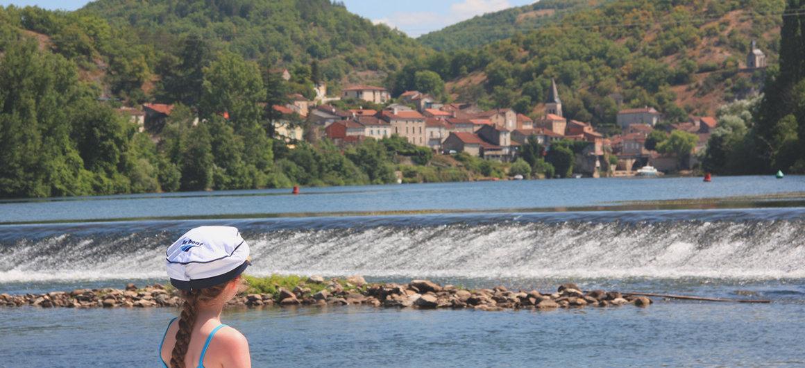 Person mit Le Boat Hut blickt auf das Wehr